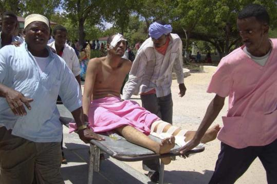 Relatives helped remove one of the victims of yesterday's attack in Mogadishu, Somali, from the scene. No lawmakers were killed or wounded in the attack, a police spokesman said.