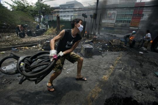 A protester threw oil-soaked inner tubes yesterday as the military warned government opponents to retreat in Bangkok.