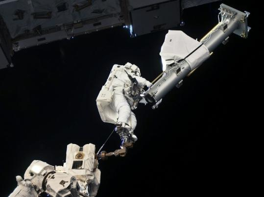 Astronaut Garrett Reisman worked outside the International Space Station, operating the robot arm. The 20-foot-long compartment installed yesterday adds a lab and a closet.