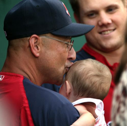 Red Sox closer Jonathan Paplebon (right) looks on as Francona gives a kiss to Papelbon's 8 month old daughter Parker in the Sox dugout before a game in August 2009.