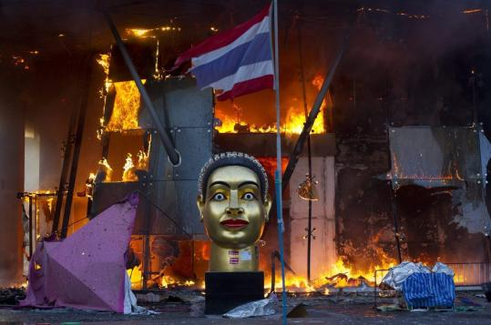 A statue of Buddha and a torn Thai national flag remained in front of Bangkok's Central World shopping mall, which was gutted by fire after army soldiers advanced toward an encampment of thousands of antigovernment protesters.