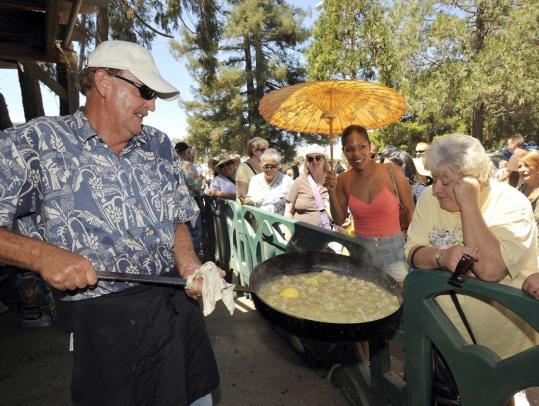 Scampi chef Pat Vickroy shows off a pan of his shrimp at last year's Gilroy Garlic Festival.