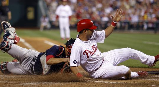 Pinch runner Juan Castro slides past the tag of Red Sox catcher Victor Martinez in the sixth inning, scoring on a single by Ryan Howard and giving the Phillies a 5-1 lead.