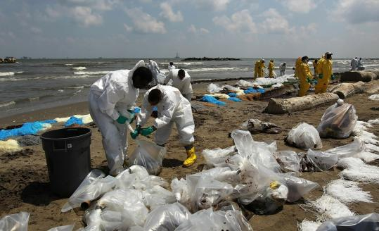 A BP cleanup crew removed oil from a beach yesterday at Port Fourchon, Louisiana. Officials now say that it may be impossible to clean the hundreds of miles of coastal wetlands affected by the massive oil spill, which continues to gush into Gulf of Mexico.