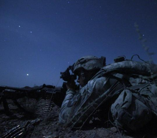 US Army Specialist Kevin O'Connor, of Hingham, Mass., kept a lookout in the dark for Taliban fighters who fired on his Kandahar Province outpost over the weekend.