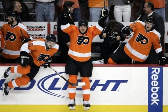 Danny Briere (left), Claude Giroux, and James van Riemsdyk begin celebrating after the Flyers advanced to the Cup finals.