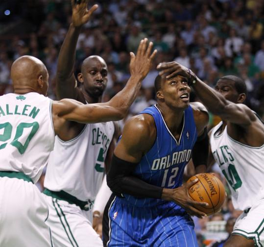 Yoon s. byun/Globe Staff Ray Allen (left), Kevin Garnett, and Michael Finley (right) employ defensive tricks but they can't stop Dwight Howard.