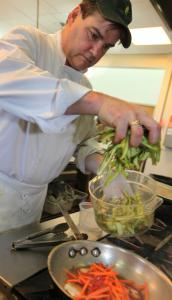 Kevin Carey, chef at Verrill Farm in Concord, prepares asparagus and scallop sesame stir fry.