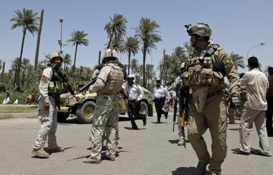 Iraqi security forces stood guard at a checkpoint in Baghdad yesterday not far from where the jewelry market area was robbed.