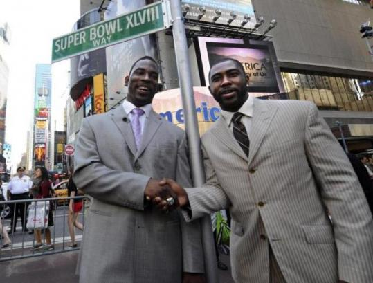 Justin Tuck of the Giants (left) and Jets' Darrelle Revis celebrated the 2014 Super Bowl vote in Times Square.