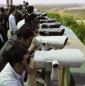 Visitors looked at the North Korean side through binoculars at an observation post in the demilitarized zone near the border village of Panmunjom yesterday.