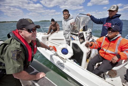 Jason DeJackome, an officer with the Massachusetts Environmental Police, spoke with some boaters in Boston Harbor to make sure they had proper safety equipment.