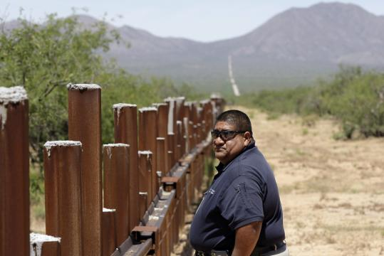Sergeant Vincent Garcia of the Tohono O'odham Nation police walked along the fence at the US-Mexico border in San Miguel, Ariz. Smugglers use blowtorches and hacksaws to penetrate it.