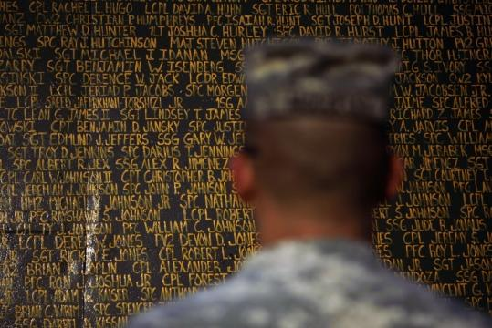 Sergeant Kevin McCulley stood before a memorial in Kirkuk. It was created last year when volunteers painted the names of US service members who died in Iraq on blast barriers.