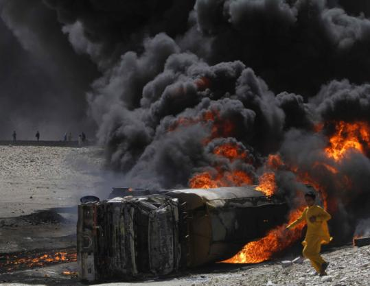 A boy ran past a burning tanker carrying fuel for NATO forces Friday near Kabul. It was allegedly attacked by Taliban forces.