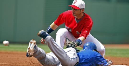 Marco Scutaro receives a throw from Jason Varitek, nabbing the Royals' Willie Bloomquist stealing in the first.