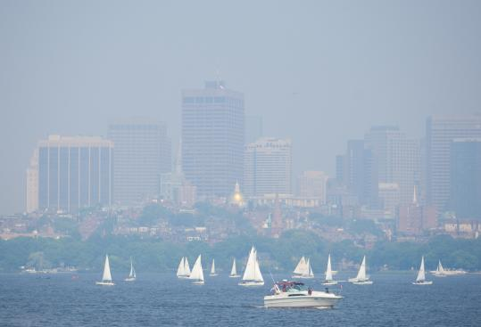 On an unusually hazy day in May, the Boston skyline provided a smoky backdrop as boaters enjoyed Memorial Day on the Charles River. At one point, the Prudential building was not visible from the Allston-Brighton tolls on the Massachusetts Turnpike.