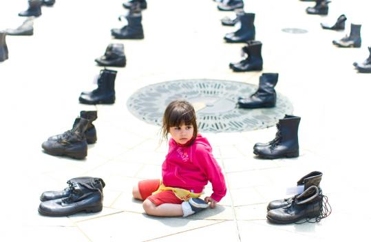 Maram Ahmed, 3, sat among military boots commemorating troops from Massachusetts at a peace rally in the North End.