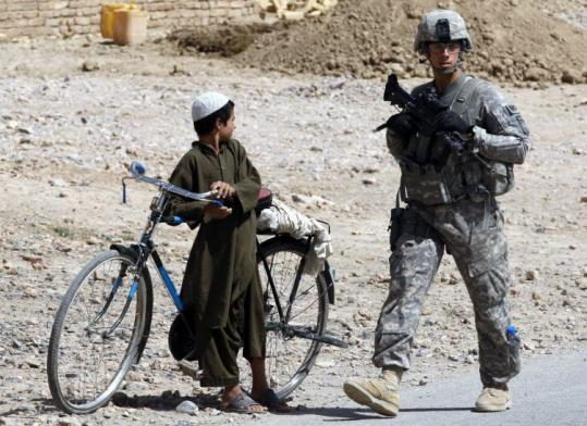 A US soldier walked past an Afghan boy as he provided security for aid workers last week in Kandahar. Two aid groups, American and Norwegian, have been accused of proselytizing.