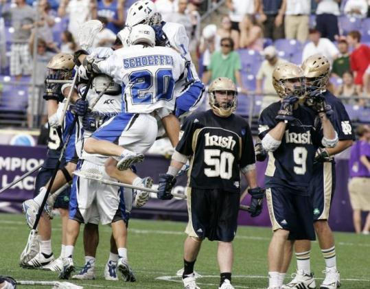 Steve Schoeffel (20) jumps into the celebration after Duke beat Notre Dame on C.J. Costabile's goal five seconds into overtime.