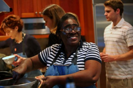 Anette LaMontagne, from Haiti, helps chef Jody Adams (far left) cook a goat.