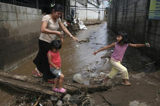 A woman and two children crossed a flooded alley yesterday after the Mico River overflowed in Amatitlan, Guatemala.