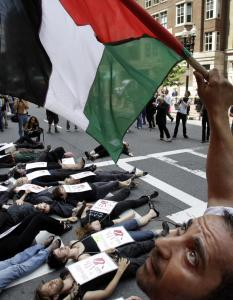 "Mouatassem Elawad waved a Palestinian flag during a ""die-in'' that about 100 protesters staged outside the Israeli Consulate at Boston's Park Plaza yesterday."