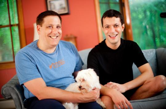 Tim Coco (left) with Genesio Oliveira and their dog, Q-tip, at home in Haverhill yesterday. Oliveira can now try again for legal residency.