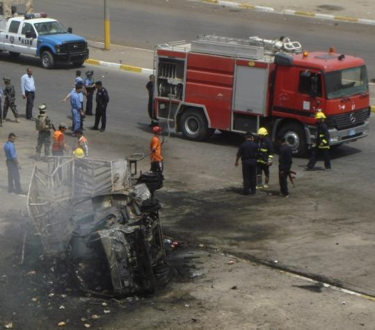 Firefighters and security personnel gathered near a vehicle damaged by a bomb outside a police station in Baghdad. Four police officers and one civilian were killed, and 15 people were injured in the blast, which occurred officers gathered outside for a shift change.