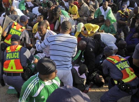 Police restrain fans prior to warm-up match between North Korea and Nigeria after thousands stampeded outside the stadium gates.