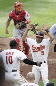 The celebration is on when Cesar Izturis (3) scores for the Orioles in the 11th inning.