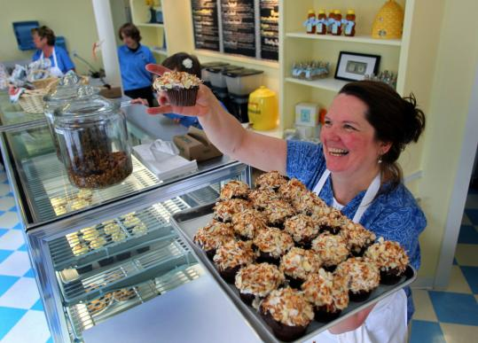 Elin Agustsson held up one of her signature cupcakes in her new Busy Bee Bakery in Melrose. A loan from East Boston Savings Bank helped Agustsson open the bakery.