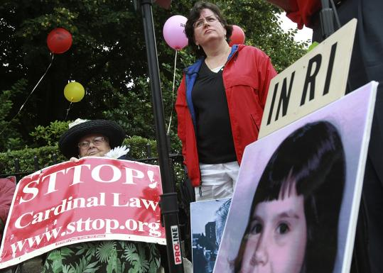 Helen McGonigle (standing) and Rosemary Morgan were among protesters outside the Cathedral of the Holy Cross yesterday.