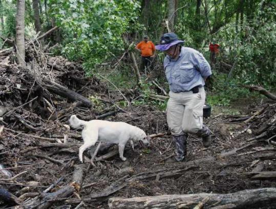 Dr. Carol Gilbert, of Roanoke, Va., and her search dog Moki scoured a debris pile where a flash flood raged Friday.