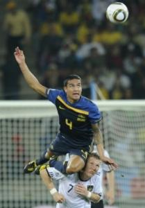 Australia's Tim Cahill (top) heads the ball with an assist from Bastian
