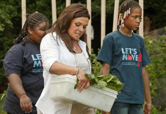 Rachael Ray harvests vegetables with elementary students in the White House garden.