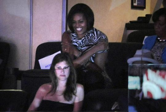 First lady Michelle Obama and an unidentified fan watch from a luxury box.