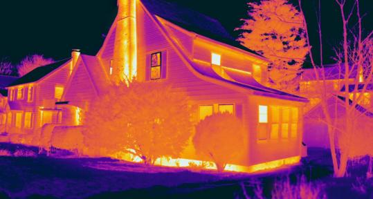 Infrared cameras reveal buildings' insulation leaks. Light colors, like the yellow along the foundation and chimney, signal heat loss.
