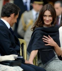 Carla Bruni-Sarkozy reached out for the hand of her husband, President Nicolas Sarkozy of France, during a parade at The Royal Hospital Chelsea in London.