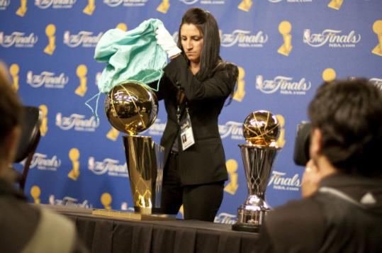 The hardware was in the capable hands of NBA staffer Jaralai Christiano, who kept telling herself not to fall as she brought the trophies into place.
