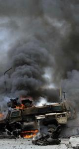 A NATO vehicle burned following a suicide attack recently in Jalalabad, Afghanistan. Trucking companies that supply US forces say they must pay warlords and Afghan officials for protection so their convoys can pass unhindered.