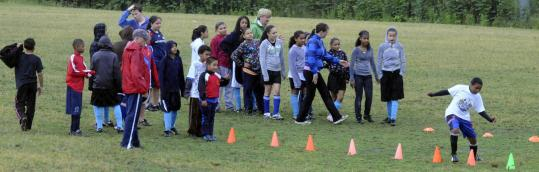 Ellen and Stephanie McArdle run Lawrence girls and boys through drills at a recent soccer practice.