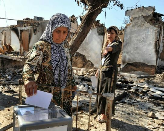 Uzbek women voted in the yard of their burned house in Kyrgyzstan. Thousands fled ethnic violence in recent weeks.