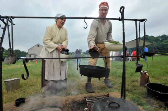 Aided by Ann Swartzell, Stephen Banatoski simmers barley with herbs for His Majesty's 10th Regiment of Foot during a reenactment at Spencer-Peirce-Little Farm in Newbury.