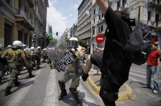 A demonstrator kicked a policeman during a clash in Athens yesterday. It was the fifth general strike in Greece this year.