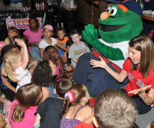 Wally the Green Monster and Kelli Pedroia read to children at Fenway.