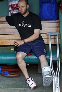 Sign of the times: Dustin Pedroia, one of a number of injured Red Sox, watches batting practice from the dugout, crutches close at hand.