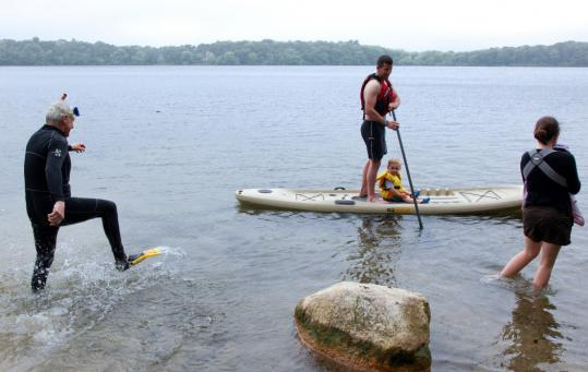 On Hamblin's Pond in Marstons Mills, Jeff Craddock takes son Timothy for a kayak ride while his wife, Anne, wades with baby Caitlin. His father, James Craddock, is going snorkeling.