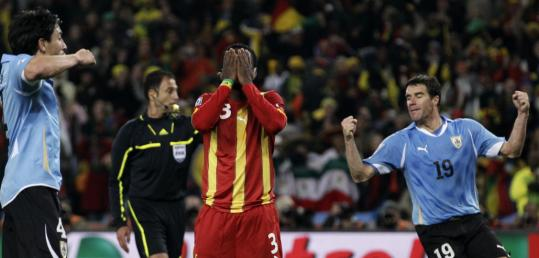 Jorge Fucile and Andres Scotti celebrate Ghana's Asamoah Gyan's missed penalty kick.