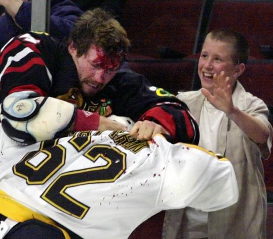 Bob Probert (left) often had the upper hand in fights. In 2001, he and Bruin Andrei Nazarov tangled, to the delight of a fan.